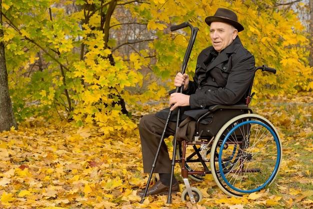 Homem idoso com deficiência em uma cadeira de rodas, sentado de sobretudo e chapéu em uma floresta colorida de outono