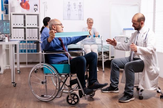 Homem idoso com deficiência fazendo exercícios no hospital com o médico