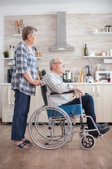 Homem idoso com deficiência sentado em uma cadeira de rodas na cozinha, olhando pela janela. viver com pessoa com deficiência. esposa ajudando marido com deficiência. casal de idosos com casamento feliz.