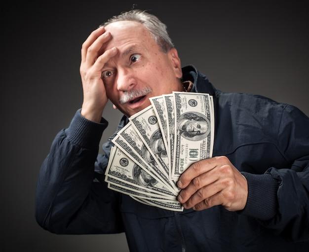 Homem idoso com fã de dólares