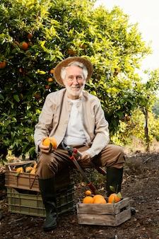 Homem idoso com laranjas frescas