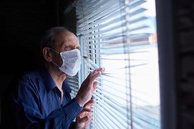 Homem idoso com máscara médica está em quarentena e auto-isolamento