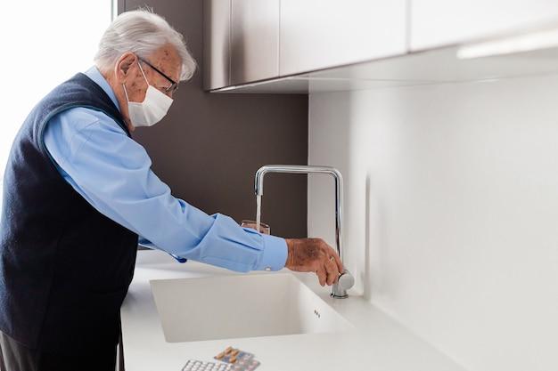 Homem idoso com máscara vestindo camisa azul e colete azul, colocando um copo de água da torneira na cozinha para tomar os comprimidos.
