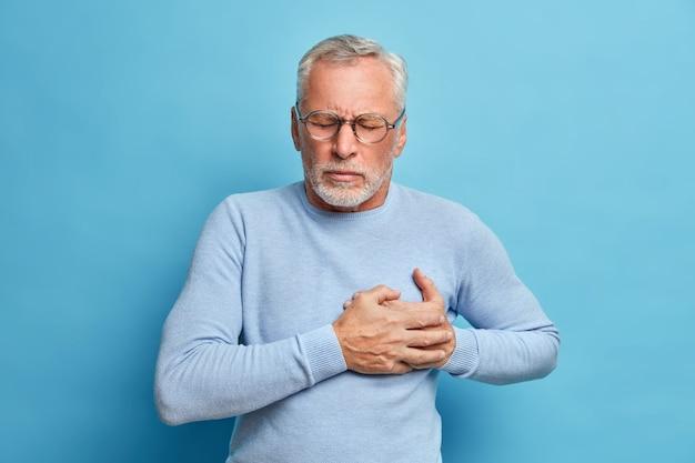 Homem idoso com óculos pressiona a mão no peito, tem ataque cardíaco, sofre de uma dor insuportável, fecha os olhos e usa óculos ópticos poses contra a parede azul