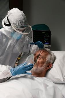 Homem idoso com respirador em uma cama de hospital
