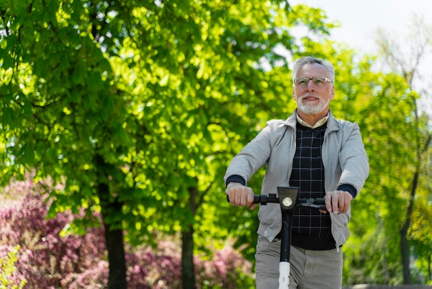 Homem idoso com scooter ao ar livre