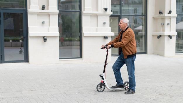 Homem idoso com scooter em tiro médio