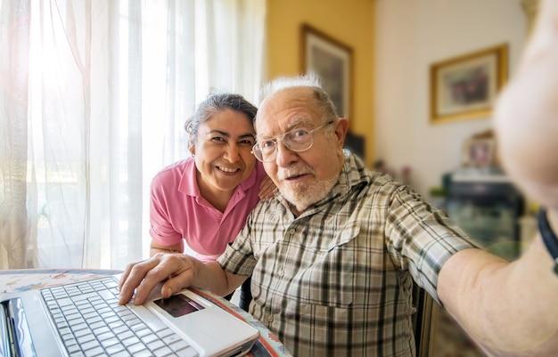 Homem idoso com seu cuidador tirando uma foto de selfie em casa