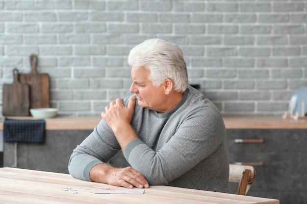Homem idoso com síndrome de parkinson em casa