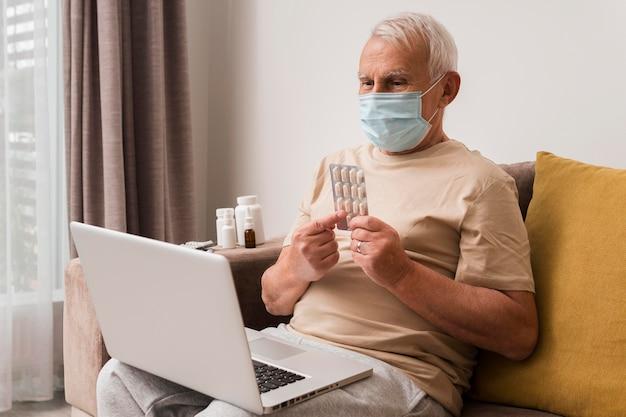Homem idoso com tiro médio segurando bolhas de comprimidos