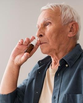 Homem idoso com tiro médio usando spray nasal