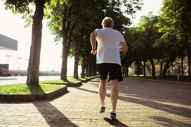Homem idoso como corredor com braçadeira ou rastreador de fitness nas ruas da cidade