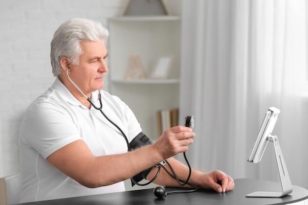 Homem idoso conversando por vídeo com médico em casa