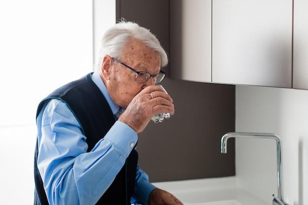 Homem idoso de camisa azul e colete bebendo um copo d'água na cozinha de sua casa.