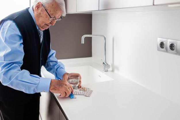 Homem idoso de camisa azul e gravata se preparando para tomar o remédio na cozinha de sua casa.