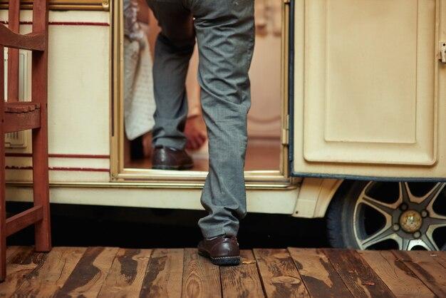 Homem idoso de jeans entrando em seu motorhome
