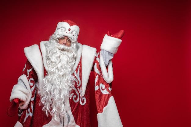 Homem idoso de papai noel com traje festivo de natal apontando com a mão para copiar o espaço no vermelho
