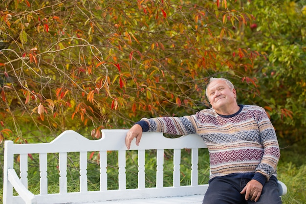 Homem idoso descansando no banco branco no parque outono