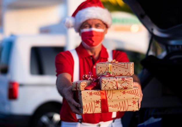 Homem idoso desfocado fazendo compras para o natal com um chapéu de papai noel e suspensórios segurando presentes