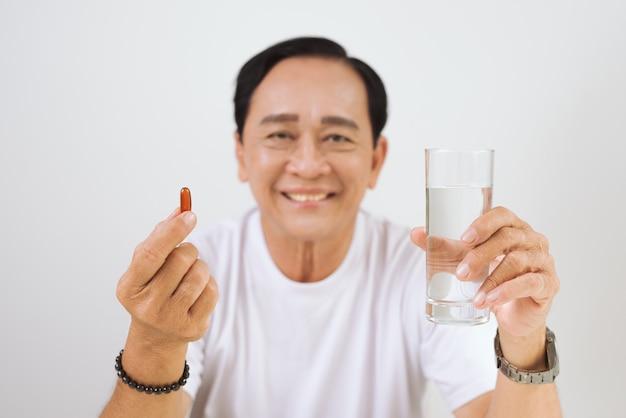 Homem idoso doente com vitamina / ômega 3 nas mãos.