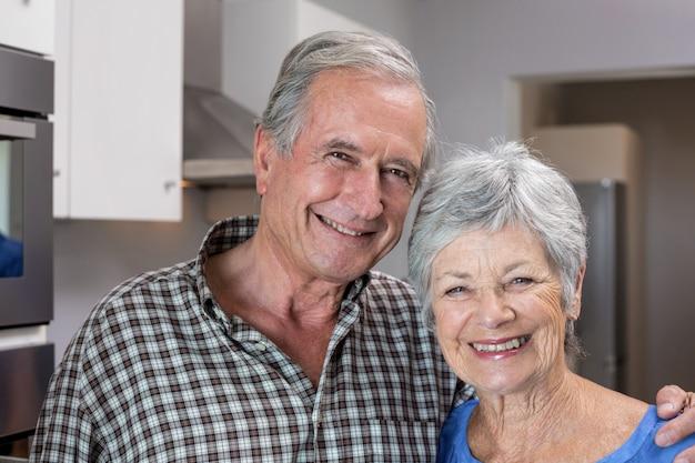 Homem idoso e mulher em pé na cozinha