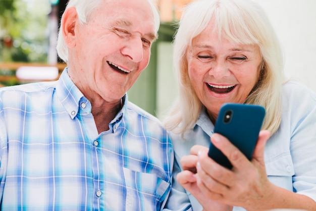 Homem idoso, e, mulher, usando, smartphone, sorrindo
