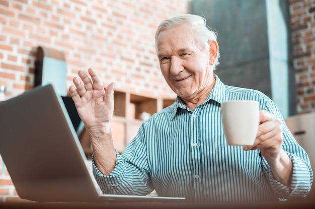 Homem idoso e positivo segurando uma xícara de chá e mostrando um gesto de saudação enquanto faz uma videochamada