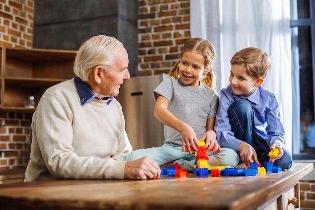 Homem idoso e simpático, reunindo blocos de construção com seus netos