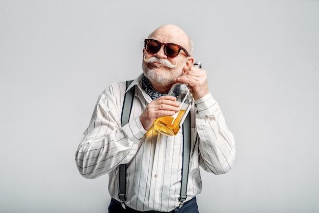 Homem idoso elegante abraça a garrafa de uma boa bebida alcoólica. sénior maduro, cara