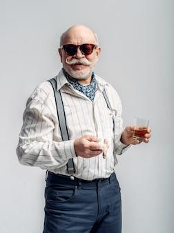 Homem idoso elegante com charuto e uma garrafa de álcool bom. sénior maduro, cara