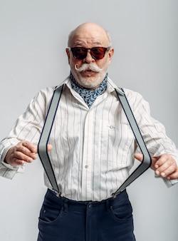 Homem idoso elegante em calças com suspensórios e óculos de sol. sénior maduro, cara