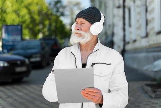 Homem idoso em foto média usando fones de ouvido