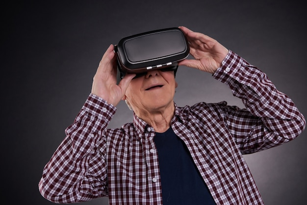 Homem idoso em óculos de realidade virtual em fundo preto.