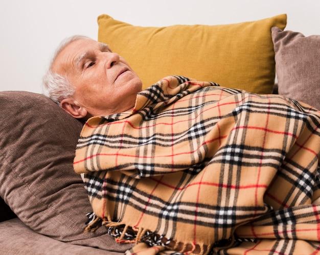 Homem idoso em plano médio deitado no sofá