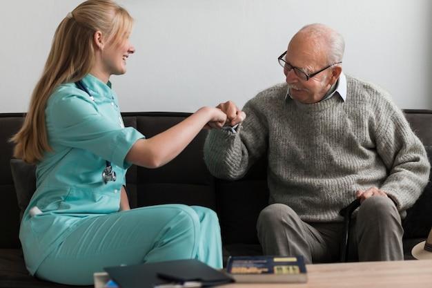 Homem idoso em uma casa de repouso com os punhos da enfermeira