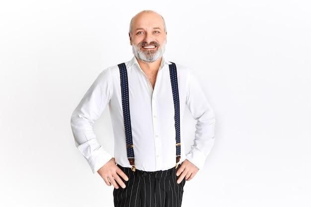 Homem idoso emocional feliz com barba grisalha e cabeça careca regozijando-se, segurando as mãos na cintura, sorrindo alegremente, posando contra um fundo branco com espaço de cópia para o seu texto