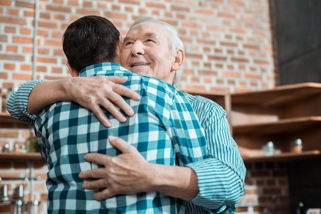 Homem idoso encantado abraçando seu filho e sorrindo enquanto expressa seu amor por ele