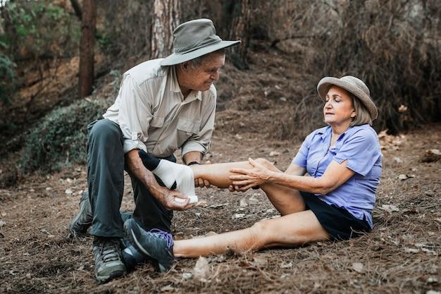 Homem idoso enfaixando o tornozelo da esposa