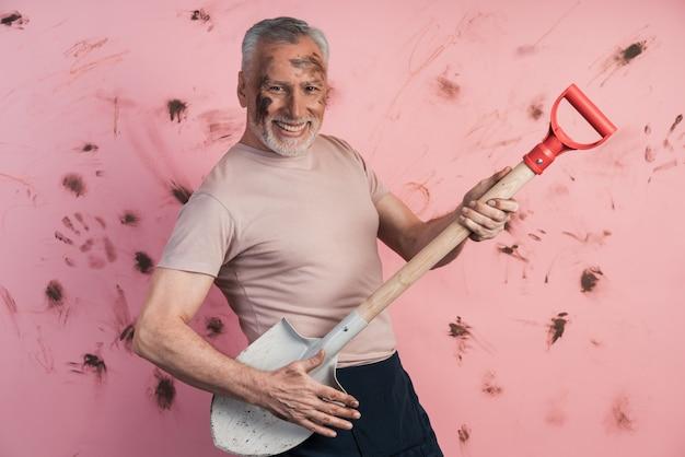 Homem idoso, engraçado, alegre, segurando uma pá como se estivesse segurando um violão