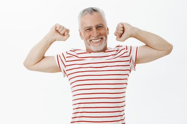 Homem idoso, entusiasmado e feliz, se alongando e sorrindo satisfeito