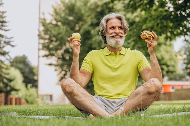 Homem idoso escolhendo entre hambúrguer e maçã