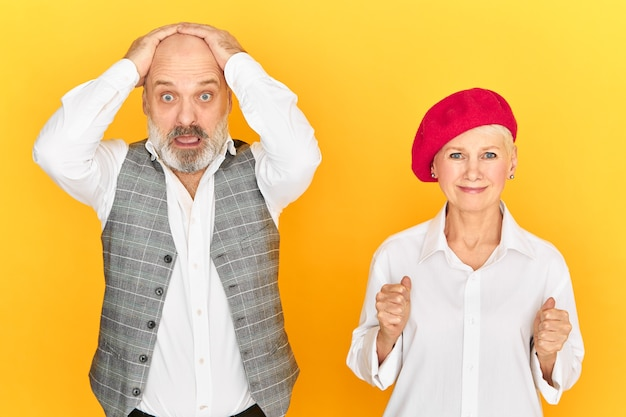 Homem idoso estressado com barba de mãos dadas na cabeça e olhando para a câmera com total descrença, entrando em pânico, sua esposa tentando apoiá-lo