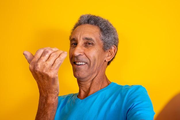 Homem idoso fazendo selfie e chamando com a mão 'vem cá' '.
