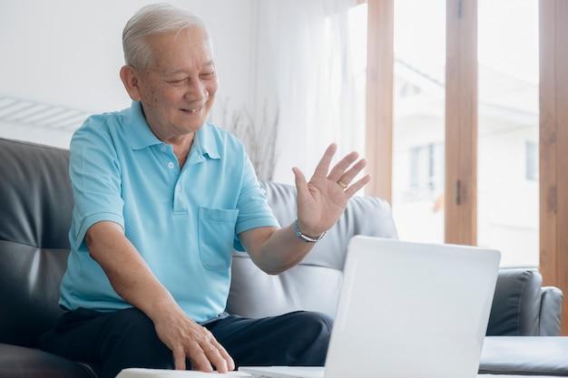 Homem idoso fazendo videochamada e acenando para a tela