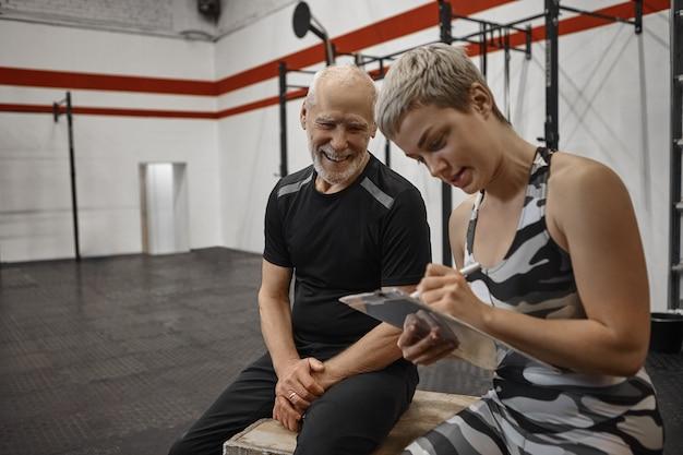 Homem idoso feliz carismático com corpo atlético musculoso sentado no centro de fitness com uma jovem treinadora loira que está anotando os resultados após o treino pessoal com seu cliente sênior