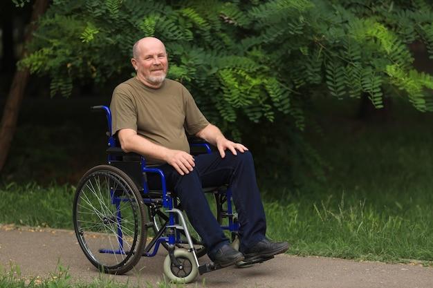 Homem idoso feliz com deficiência sentado em cadeira de rodas ao ar livre no verão