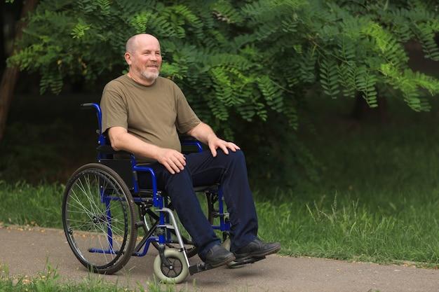 Homem idoso feliz com deficiência sentado em cadeira de rodas ao ar livre