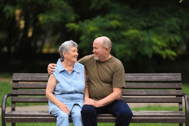 Homem idoso feliz e mulher com deficiência sentados em um banco ao ar livre no parque