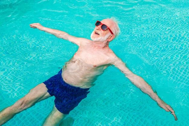 Homem idoso feliz fazendo festa na piscina - idoso ativo tomando banho de sol e relaxando em uma piscina privativa durante o verão