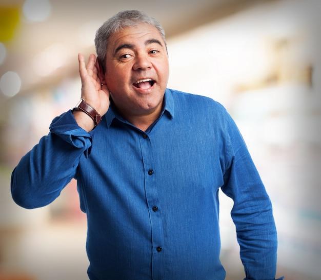 Homem idoso fingindo não ouvir com uma mão em seu ouvido